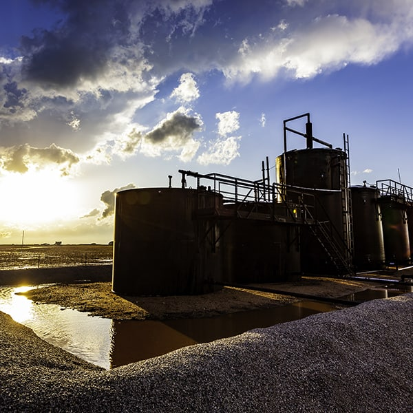 Farm Oil Storage Tanks With Stormy Sunset And Sunflare